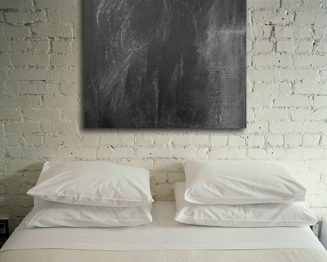 Contemporary Abstract painting that is black and white hanging above bed