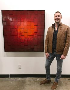 Andy Hahn artist standing with his modern abastract painting
